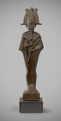 Egyptian bronze statuette of Osiris.  Ptolemaic Period. 3rd - 2nd century BC.  This sizeable bronze figure depicts the god standing upright and mummiform on an integral trapezoidal base. He holds the traditional symbols of royalty, the crook and flail, to his chest and wears the plumed and horned Atef crown with frontal uraeus. A braided beard at his chin and a broad collar incised. The eyes retain their original silver inlay.  Height: 34 cm