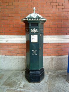 Queen Victoria postbox in Windsor.The first pillar post boxes were erected in Jersey in 1852. In1856 Richard Redgrave of the Department of Science & Art designed an ornate pillar box for use in London & other  cities.Green was adopted as the standard color for the early Victorian post boxes.The first boxes to be painted red were in London in July 1874.