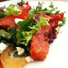 Roasted Tomato Salad | Roasted tomatoes with onion and herbs are served warm atop tender lettuce leaves with shaved Parmesan cheese in this summery salad.