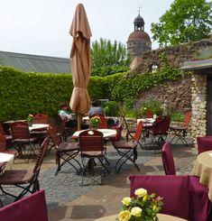 Der malerische Garten des Café Lucullus in Görlitz. Hier lässt sich hervorragend eine Mohnpiele zum Cappuccino genießen. Im Hintergrund ist der Nikolaiturm zu sehen.