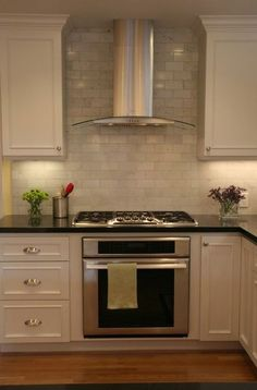 Carrera marble backsplash with black counter-tops -- hardware might be better in bronze to pull in floor and warm this up?