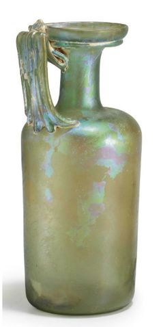 A ROMAN GLASS JUG   CIRCA 1ST-2ND CENTURY A.D.   Pale yellow-green in color, free blown, the cylindrical body on a flat base, with rounded shoulders, a long cylindrical neck and a funnel-shaped mouth, an applied ring on the underside of the mouth, the ribbed strap handle folded along the underside of the rim, the body with thin horizontal wheel-cut bands  9 3/8 in. (23.7 cm.) high