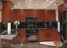 cherry wood cabinets with black granite counter tops