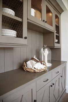 In a small nook, this beautifully appointed gray butler's pantry is equipped with gray custom lit cabinets accented with chicken wire doors and fixed to a gray shiplap backsplash above a gray countertop complementing gray diamond pattern cabinet doors finished with oil rubbed hardware.