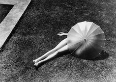 Nude with Parasol, munkacsi 1935.  Wait a minute - this is Pinterest. Non-nude woman with a t-shirt obscured by a parasol. Phew!