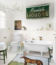 Upstate New York bathroom of Country Living's editor-in-chief Sarah Gray Miller. Liquor store sign and horse rug decorate whitewashed pine beadboard and floor, which replaced blue tile. Salvage tub is from Zaborski Emporium in Kingston, N.Y.