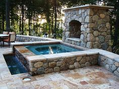 Stone and travertine marble hot tub with fireplace and water feature.