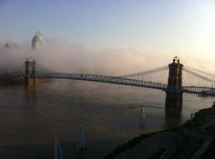 Roebling Suspension Bridge: Early morning fog rolling down the Ohio under the bridge -- Cincinnati