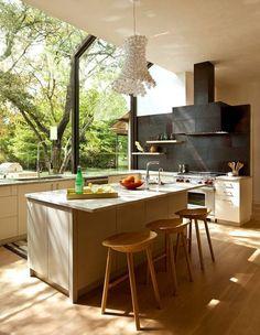 der kochbereich-kochinsel mit spülbecken-designer hängelampe und hölzerne Barstühle