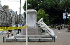 People walk past a fallen statue in the Christchurch, New Zealand after the earthquake