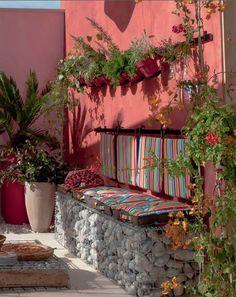 décoration terrasse avec banquette fabriquée avec galets et coussins rayures