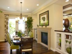 The formal dining room shares a two-way fireplace with the living room. Low cabinets on either side of the fireplace keep the room from feeling closed off. The color scheme and textiles are tasteful and tropical in style.