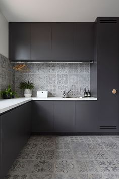 In this modern laundry room, matte black cabinets provide a strong contrast to the light grey tiles and the white countertops. A drying bar has been i… – Laundry Room Modern Laundry Rooms, Laundry Room Layouts, Modern Room, White Kitchen Backsplash, White Countertops, Backsplash Ideas, Interior Design Kitchen, Home Design, Home Renovation