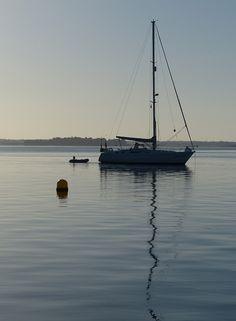 Ombre chinoise et réflexion. Voilier au mouillage au sud de l'Île d'Arz. Bretagne.
