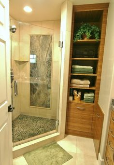 love the forest green marble slab framed by tile moulding on shower wall!  and pebbles shower floor!