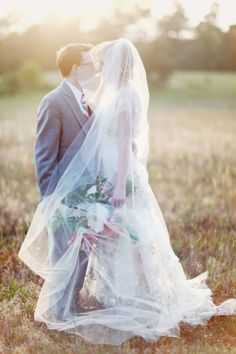 bride in lace wedding dress with large pink, white and red bouquet standing in a grass field with groom in grey suit under a veil at spring / summer outdoor wedding | Simply Charming Socials | Atlanta Wedding Planner