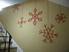 Popsicle stick snowflakes hanging from the wall going up the stairs