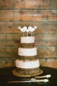 Three tier burlap wrapped rustic wedding cake: http://www.stylemepretty.com/california-weddings/petaluma/2017/02/23/unique-floral-motif-wedding-dress-for-a-dream-rustic-wedding/ Photography: One Love - http://www.onelove-photo.com/