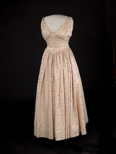 Mamie Eisenhower wore a pink peau de soie gown embroidered with more than 2,000 rhinestones to the 1953 inaugural balls. The dress was designed by Nettie Rosenstein.  Despite urgings to release details of the dress, Mrs. Eisenhower waited until the week before inauguration to reveal descriptions of her sparkling pink gown, along with formal photographs, for the newspapers.