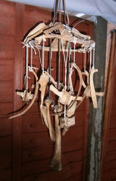 Bone wind chime by Twisted Endeavors. Boil real bones until any residual meat/cartilage comes off. Brush/scrub anything else left completely off. Soak in hydrogen peroxide until bleached & sanitized. Drill holes.