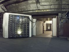 50th anniversary of the opening of the North American Aerospace Defense Command Combat Operations Center inside Cheyenne Mountain. 1/3rd mile inside the main access tunnel are a pair of steel blast doors leading to the main complex. Each is 25 tons, is 11 ft high by 13 ft wide, 3 1/2 ft thick, and are spaced 50 ft apart. They are encased in reinforced concrete collars 17 ft thick, and can be closed & locked by a hydraulic pump within 30 to 45 seconds. Or can be manually closed in 4 1/2…