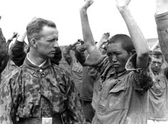 """Waffen SS officer with Soviet POWs. He is staring in particular at an Asiatic """"subhuman"""" -- and perhaps wondering how fast he can dispatch him for good."""