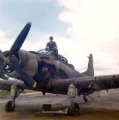 A soldier stands in the cockpit of a damaged Douglas A-1 Skyraider at the Kontum airfield.