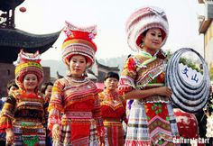Miao women wearing silver headdress and ethnic costumes get together to demonstrate their traditions to tourists and local inhabitants in an ethic group area - Hunan province's Fenghuang county.
