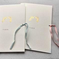Takkekort til dåp og navnefest med håndtrykt babyfotavtrykk i gull og nydelig bånd i ekte matt silke i lys blått eller rosa.
