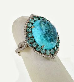 "Evening Wear - 1st Place: Platinum and white gold ""Blue Fin"" ring by Leon Mege of Leon Mege, Inc. This ring features a 12.75 ct. Paraiba Tourmaline cabochon accented with diamonds."
