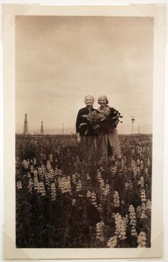 Two people in a field of flowers, holding flowers.