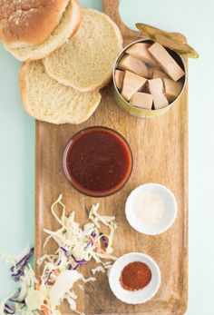 hamburger buns, bbq sauce, coleslaw, jackfruit, and seasonings on wooden board Jackfruit Sandwich, Jackfruit Recipes, Barbeque Sauce, Bbq, Vegan Foods, Vegan Recipes, Hamburger Buns, Coleslaw, Pulled Pork