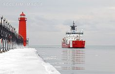 Stock Photo of New Coast Guard Cutter Mackinac and the Grand Haven, MI Lighthouse