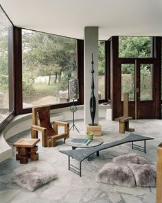 A seventies house in Dinard In the beautiful rounding of the living room, the assises are signed Dominique Zimbacca, the two low tables, in pyrite and inlaid marquetry, are by Pia Manu (the Yves Gastou Gallery), the lamppost by François Thévenin and The bronze totem of François Stahly.