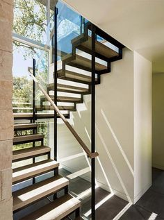Wood and steel stairs lead you to the upper floor of this home, with large windows flooding the area with sunlight. Staircase Handrail, Staircase Remodel, Staircase Design, Staircase Ideas, Sustainable Architecture, Architecture Details, Landscape Architecture, Glass Stairs, Stairs Window