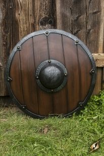 This Viking Shield is a round 69 cm latex shield inspired by early century Vikings and Saxons ones. With a wooden texture and wood and iron paint finish. Made of hard EVA foam and latex.
