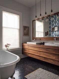 Long wood counter in this bathroom, pendant lights, larger mirror and double sinks.