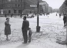 An East German woman stands crying after she passed a young boy to a man in West Berlin over a barbed wire fence separating East and West Berlin (1961)