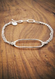 A jewelry designer David suggested to me: Melissa Joy Manning. This bracelet is an example of jewelry with the elements of silver, oval, and open work he likes for me.