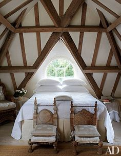 Oak beams crisscross the ceiling in a top-floor guest room in an English manor.