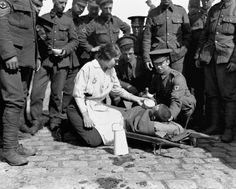 Civilians and soldiers of the Royal Army Medical Corps distribute refreshments to British wounded in France, 1916.
