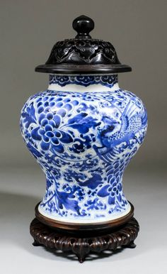 A Chinese blue and white porcelain baluster shaped vase painted with dragons, flowers and cloud motifs, 9.5ins (241mm) high (Kangxi period - small chip to footrim), with pierced hardwood cover and stand for same