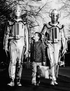 Anthony King, 10, visiting the London set of 'Dr. Who,' finds two friendly Cybermen companions. February 25, 1967.