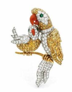 Rare clip de corsage en or jaune et platine ciselé d'un perroquet et de son petit sur une branche, Cartier, vers 1962