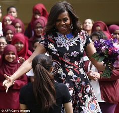 Cuddle: Michelle Obama opens her arms to embrace a student
