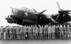 Members of No 106 Squadron RAF gather in front of an Avro Lancaster B Mark I