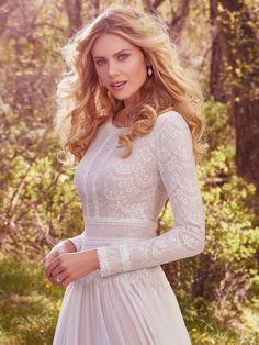 Understated elegance is found in this subtle lace and Santorini chiffon A-line wedding dress, complete with bateau neckline and long sleeves. Lace is fully lined with Inessa jersey for demure coverage. Finished with zipper closure.