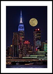 Empire State ESB Super Moon NYC - View to the iconic urban landmark of the Empire State Building lit up in white and blue. Also seen is the New Yorker Hotel, One Penn Plaza building and other structures that make up the midtown Manhattan, New York City skyline. The full moon aids in illuminating the already brightly lit skyline.   Available in color as well as in black and white. To view additional photographs please visit http://susancandelario.com