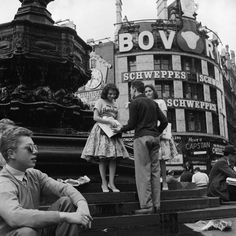 Selling newspapers from the steps of Eros, Piccadilly Circus. 1958
