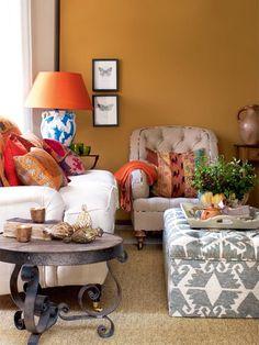 Love the orange walls, lamp and cushions!
